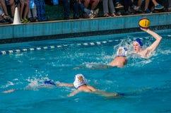 ЛЬВОВ, УКРАИНА - ИЮНЬ 2016: Игроки водного поло спортсменов воюя для шарика с оппонентами в бассейне воды в брызге Стоковое Фото