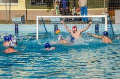 ЛЬВОВ, УКРАИНА - ИЮНЬ 2016: Игроки водного поло спортсменов воюя для шарика с оппонентами в бассейне воды в брызге Стоковое Изображение RF