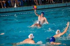 ЛЬВОВ, УКРАИНА - ИЮНЬ 2016: Игроки водного поло спортсменов воюя для шарика с оппонентами в бассейне воды в брызге Стоковое Изображение