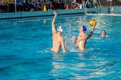 ЛЬВОВ, УКРАИНА - ИЮНЬ 2016: Игроки водного поло спортсменов воюя для шарика с оппонентами в бассейне воды в брызге Стоковое фото RF