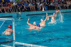ЛЬВОВ, УКРАИНА - ИЮНЬ 2016: Игроки водного поло спортсменов воюя для шарика с оппонентами в бассейне воды в брызге Стоковая Фотография