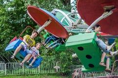 ЛЬВОВ, УКРАИНА - ИЮНЬ 2016: Молодой отец с его ездой дочери на carousel в парке атракционов, с радостными счастливыми эмоциями, h Стоковые Изображения RF