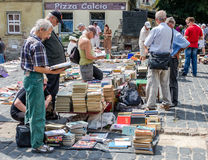Львов, Украина - июль 2015: Люди и женщины выбирают и покупка, и продавцы продают старые редкие книги и винтажные детали в метке  Стоковые Изображения