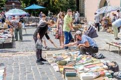 Львов, Украина - июль 2015: Люди и женщины выбирают и покупка, и продавцы продают старые редкие книги и винтажные детали в метке  Стоковая Фотография