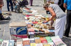 Львов, Украина - июль 2015: Люди и женщины выбирают и покупка, и продавцы продают старые редкие книги и винтажные детали в метке  Стоковое Изображение RF