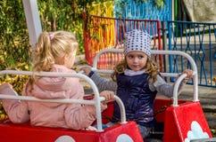 ЛЬВОВ, УКРАИНА - ОКТЯБРЬ 2017: Маленькие дети, очаровательные подруги девушек едут в парке атракционов на качании Стоковое Фото