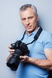 Любимая деятельность приносит максимальное удовольствие Портрет уверенно старшего человека в футболке держа камеру пока стоящ про Стоковые Фото