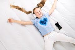 Любитель музыки: Девушка протягивает вне на большой белой кровати и слушает к музыке в больших белых наушниках стоковые изображения rf