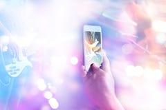 Любители музыки принимают гитариста фото на этапе в концерте на умном телефоне, мягком фокусе и тоне пастельного цвета Стоковое фото RF
