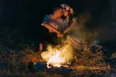 Любители природы сидя держать вручают лицом к лицу вокруг лагерного костера на ноче Стоковые Фото