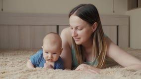 любить семьи счастливый Молодая мать играет с ее ребёнком в спальне Мама и ребенок имеют потеху на кровати видеоматериал