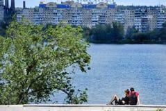 2 любовника сидят около реки на предпосылке города стоковые изображения rf