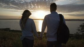 Любовники восхищают заход солнца, прогулку на речном береге сток-видео