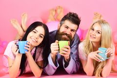 Любовники выпивая кофе в кровати Любовники в концепции кровати Человек и женщины, друзья на усмехаясь положении сторон, розовой п Стоковые Изображения RF