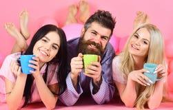 Любовники выпивая кофе в кровати Любовники в концепции кровати Человек и женщины, друзья на усмехаясь положении сторон, розовой п Стоковая Фотография