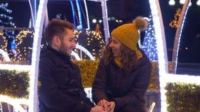 Любовники держа руки и смеясь над на одине другого на рождестве справедливо акции видеоматериалы