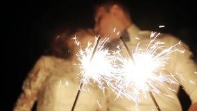 Любовники освещая бенгальские огни, празднующ свадьбу и поцелуй в нерезкости
