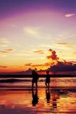 Любовники силуэта ослабляют на пляже, винтажном тоне Стоковая Фотография
