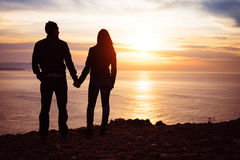 Любовники смотря заход солнца над морем Стоковая Фотография
