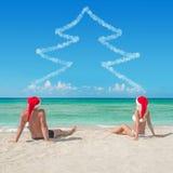 Любовники соединяют в шляпах santa на тропическом песочном beac Стоковая Фотография