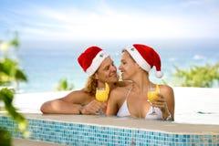 Любовники соединяют с шляпами Санты в бассейне Стоковое фото RF