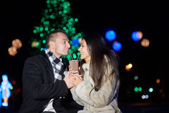 Любовники укомплектовывают личным составом и кофе женщины выпивая от кружки в зиме Стоковое фото RF
