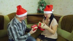 Любовники человек и женщина в Санта Клаусе покрывают подарки и поцелуй рождества обменом на Рожденственской ночи сток-видео