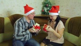 Любовники человек и женщина в Санта Клаусе покрывают подарки рождества обменом на Рожденственской ночи видеоматериал