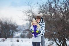 Любовники человек и женщина зимы играют с яблоками на снеге Стоковая Фотография RF