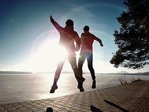 Любовники Funy счастливые скачут совместно Женщина и человек рука об руку стоковая фотография