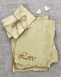 Любовные письма и конверты сделанные из античной пергаментной бумаги с деревянными сердцами на предпосылке Стоковое фото RF