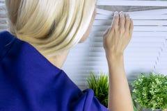 Любознательная белокурая женщина всматриваясь через белые шторки стоковые изображения rf
