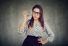 Любознательная бизнес-леди с стеклянным опарником слушая к частному разговору стоковое фото
