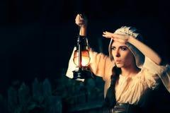 Любознательная средневековая женщина с винтажным фонариком снаружи на ноче стоковое фото rf