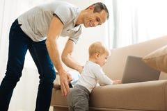 Любознательный младенец исследуя детали на софе пока счастливый усмехаться отца Стоковое Изображение