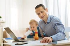 Любознательный младенец касаясь компьтер-книжке пока его занятая деятельность отца Стоковое Изображение