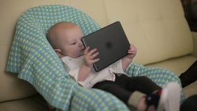 Любознательный серьезный младенец сидит на владениях стула ` s детей в его руках таблетка Конец-вверх акции видеоматериалы