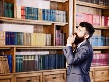 Любознательный человек выбирая книгу в его библиотеке дома стоковые фото