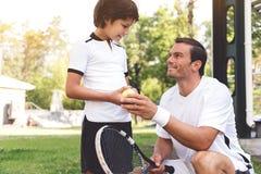 Любознательный sporty мальчик размещая около отца Стоковое Фото