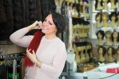 Любознательная женщина выбирая расширение волос в салон Стоковые Фото