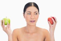 Любознательная черная с волосами модель держа яблока в обеих руках Стоковое Изображение RF