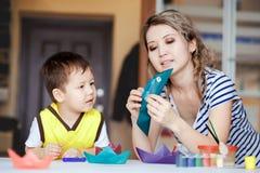 Любознательное детство, мальчик играя с его матерью, рисует, краски на ладонях Стоковые Изображения RF