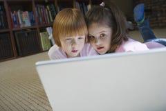 Любознательные девушки используя компьтер-книжку дома Стоковая Фотография RF