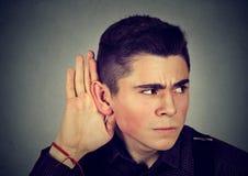 Любознательный потревоженный человек с рукой к уху слушая к сплетне Стоковое Фото