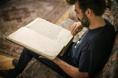 Любознательный человек читая старую книгу в его библиотеке дома стоковая фотография