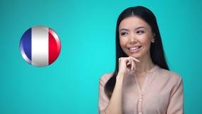 Любопытная женская нажимая кнопка флага Франции, готовая для того чтобы выучить иностранный язык видеоматериал