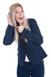 Любопытная и изумленная изолированная молодая бизнес-леди слушая на d Стоковые Фотографии RF