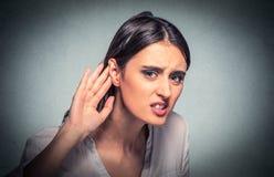 Любопытная рука женщины к уху тщательно слушает внутри на переговоре сплетни Крепко услышать Стоковые Изображения