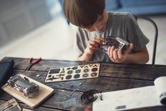 Любопытный мальчик поворачивая механизм и исправляя детали в нем стоковое изображение