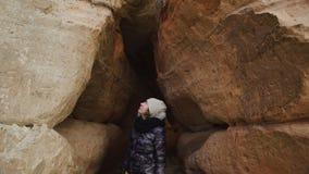 Любопытный молодой женский археолог исследуя пещеру песка - Veczemju Klintis,  акции видеоматериалы